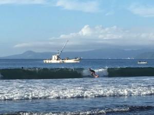 台風襲来に備えて、海水浴場のブイをあげる船と、高波に喜ぶサーファー。でも、この数時間後には、遊泳禁止になっちゃいました。
